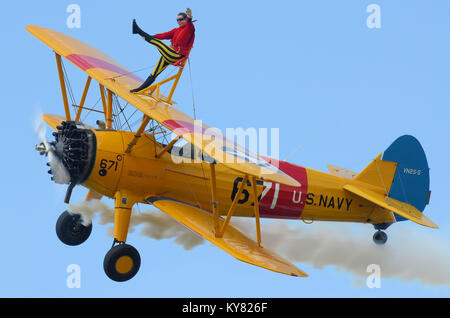 Girl Wingwalking on a Boeing Stearman biplane flying at Little Gransden Children in Need airshow. - Stock Photo
