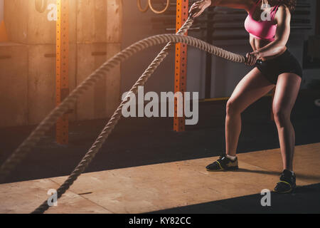 woman working out in training gym doing cross fit exercise with battle ropes - Stock Photo