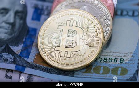 Bitcoins with US banknotes, golden bitcoin, silver bitcoin, bronze bitcoin - Stock Photo