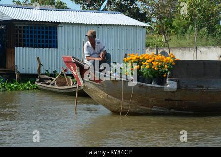 Soc Trang, Vietnam - Feb 2, 2016. A man selling flowers on Mekong River in Soc Trang, Vietnam. Mekong is the longest - Stock Photo