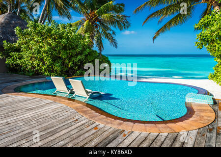 Private oceanfront pool with submerged loungers in a luxury resort in Maldives, Indian Ocean - Stock Photo