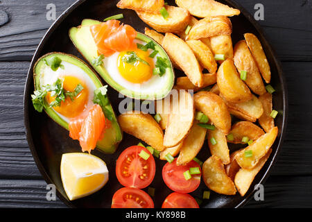 Avocado stuffed with eggs and salmon, fresh tomatoes and fried potato wedges on a plate close-up. horizontal top - Stock Photo
