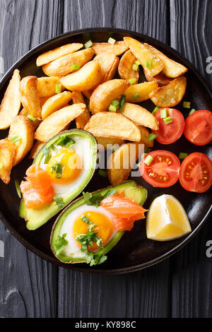 Avocado stuffed with eggs and salmon, fresh tomatoes and fried potato wedges on a plate close-up. Vertical top view - Stock Photo