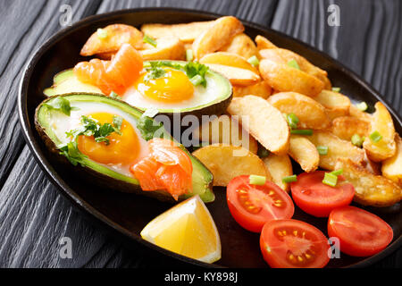 Ripe baked avocado stuffed with eggs and salmon, fresh tomatoes, lemon and fried potatoes close-up on a plate on - Stock Photo