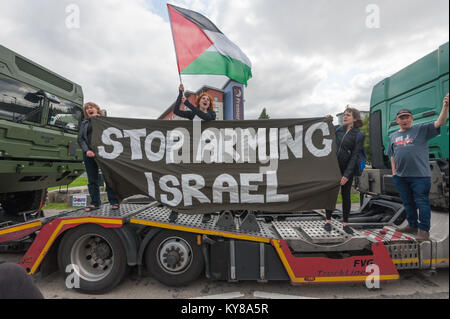 Protesters climb up onto the lorry they have stopped with a  'Stop Arming Israel' banner on the first day of a week - Stock Photo