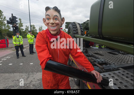 Occupy Democracy protester 'Tarpaulin Simon' wearing a Blair mask is locked on to the lorry stopped at 'Stop Arming - Stock Photo