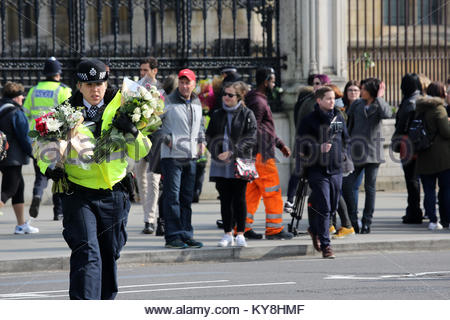 A police constable carries bouquets of flowers across the road at Westminster after the London Bridge attack. Credit:reallifephotos/Alamy - Stock Photo