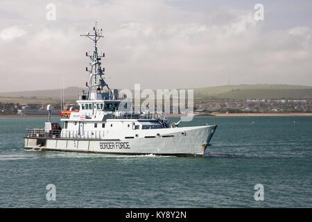 UK Border Agency customs cutter HMC Valiant passes the Stone Pier leaving Weymouth Harbour in Dorset. - Stock Photo
