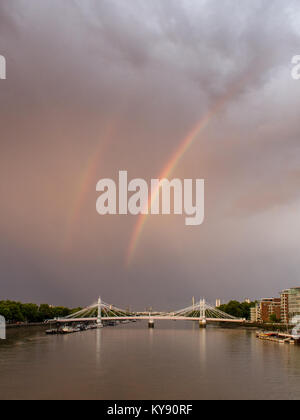 A storm passes over the River Thames and Albert Bridge at Battersea and Chelsea riversides casting a double rainbow - Stock Photo