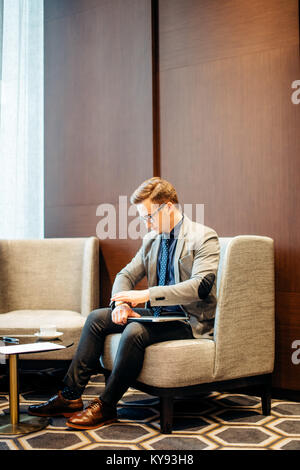 man is preparing for interview. He in suit, sitting in hall on chair, waiting - Stock Photo