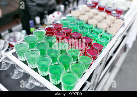row line of different colored alcoholic cocktails on a party. wedding day or birthday - Stock Photo