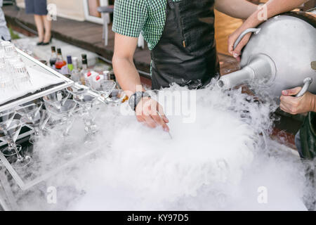 bartenders serve the cocktail in a large bowl with liquid nitrogen. row line of different alcoholic cocktails on - Stock Photo