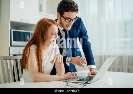 Couple enjoying time together browsing laptop. man wearing suit woman in shirt - Stock Photo