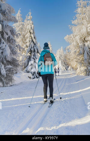 Winter road in mountains. Female skier on groomed ski trails for cross-country. Trees covered with fresh snow in - Stock Photo