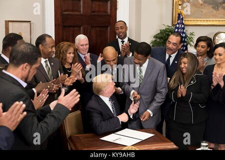 U.S. President Donald Trump hands the pen used to sign a proclamation to honor Dr. Martin Luther King, Jr. Day to - Stock Photo