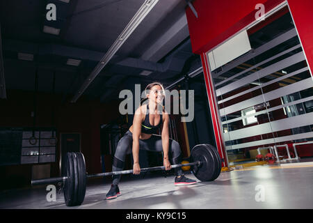 Young athletic woman doing deadlift with barbell - Stock Photo