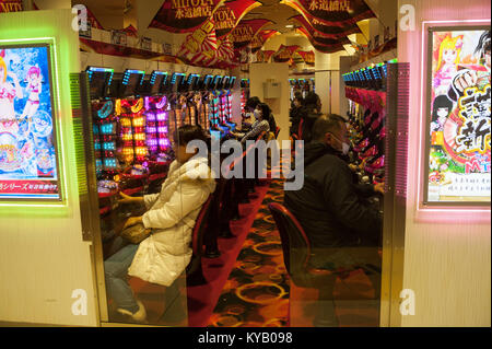 30.12.2017, Tokyo, Japan, Asia - Japanese people play with the Pachinko gaming machines in a parlour in Tokyo. - Stock Photo