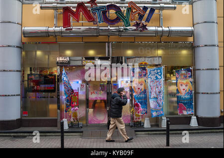 31.12.2017, Tokyo, Japan, Asia - A man walks by a Pachinko parlour in Tokyo on an early morning. - Stock Photo