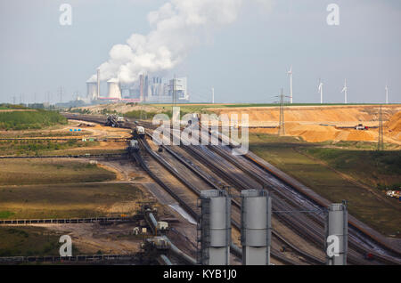 A brown coal surface mine with conveyor belts leading to a distant coal power station. - Stock Photo
