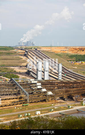 A brown coal pit mine with conveyor belts leading to a distant coal power station. - Stock Photo