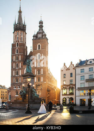 Beautiful and young bride and groom walking near the ancient building. Church of St. Mary in the main Market Square. - Stock Photo