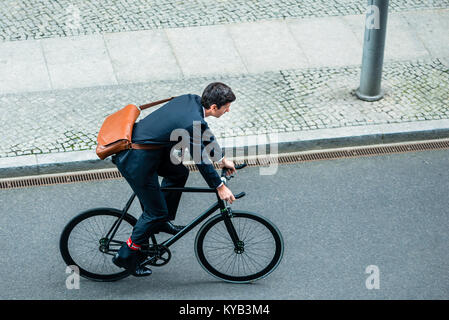Young man wearing business suit while riding an utility bicycle - Stock Photo