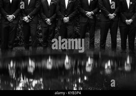 The groomsman in blue suits stand in a row. - Stock Photo