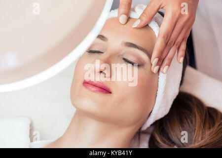 Relaxed woman smiling under the benefits of anti-aging facial ma - Stock Photo