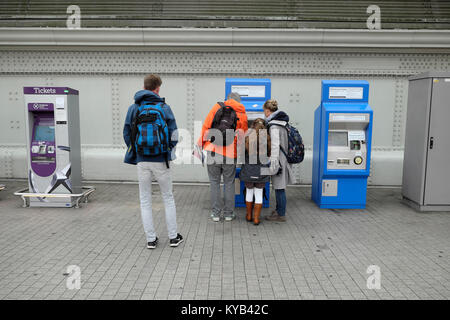 A man standing waits for a family to buy train tickets from a new ticket machine at Paddington Station in London - Stock Photo