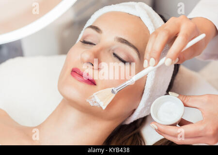 Close-up of a beautiful woman relaxing during facial treatment i - Stock Photo