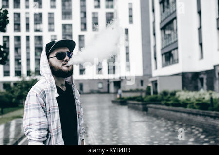 young man with beard in light checkered jacket with hood walking freely around city - Stock Photo