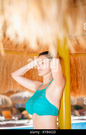 portrait of a brunette woman on the beach under a palm umbrella. Vocation and relaxing. Egypt - Stock Photo