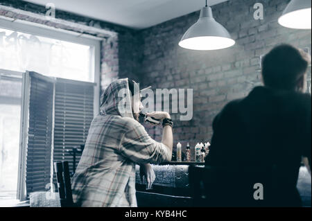 young man with beard in light checkered jacket with hood in a cap smokes an electronic cigarette in vape bar - Stock Photo