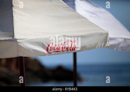 SOFIA, BULGARIA - SEPTEMBER 24, 2017: Coca-Cola text on umbrela near sea beach. Coca-cola is the world's most selling - Stock Photo