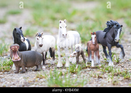 Children's toys, group of Schleich model horses and a hippo - Stock Photo