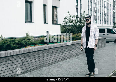young man with beard in light checkered jacket with hood in a cap and sunglasses walking freely around city smokes - Stock Photo