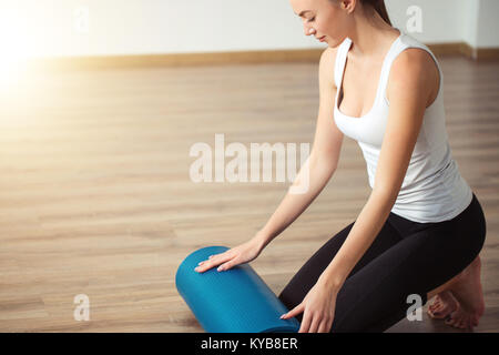 woman practicing yoga, preparing for exercise, unrolling or rolling yoga mat - Stock Photo