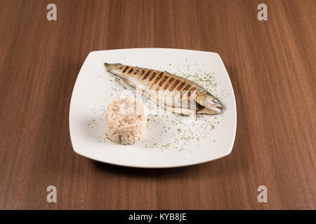 Grilled trout with rice on a with dish - Stock Photo
