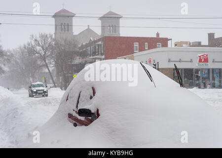 Montreal, CANADA - 13 January 2018: a car is covered with snow during snow storm in the Plateau neighborhood. - Stock Photo