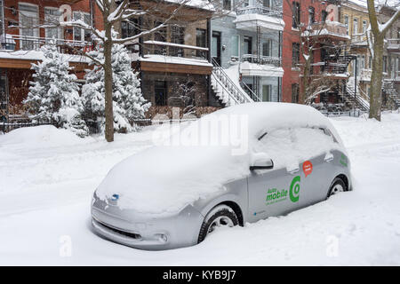 Montreal, CANADA - 13 January 2018: Car sharing Communauto vehicule buried in snow during snow storm - Stock Photo