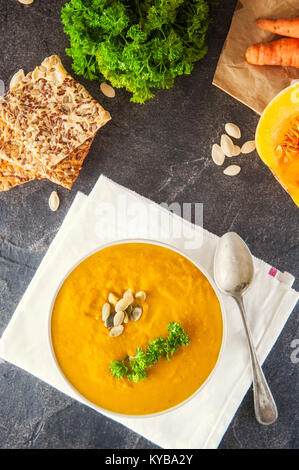 Bowl of Roasted pumpkin and carrot cream soup with parsley and pumpkin seeds on the dark stone served table with - Stock Photo