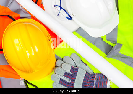 Yellow and white hard safety hats with protective gloves and glasses laying on a pile of hi vis vests - Stock Photo