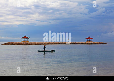 Balinese fisherman in a traditional outrigger wooden boat, wearing a conical hat, paddles in the lagoon at Sanur - Stock Photo