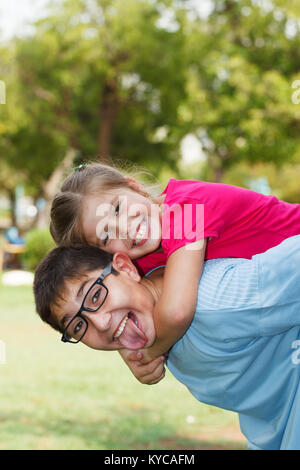 Children playing piggy back, looking at the camera. - Stock Photo