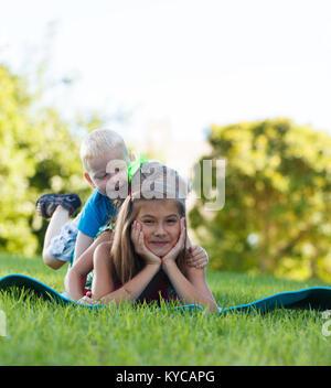 Happy children playing piggy back - Stock Photo