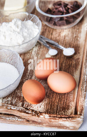 Baking ingredients for chocolate cake muffins or cookies lying ready on wooden kitchen tray - Stock Photo
