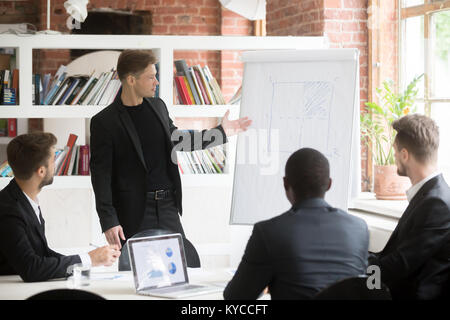Confident businessman presenting project to diverse investors at office meeting, ceo giving flip chart presentation, - Stock Photo