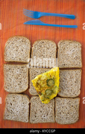 sliced wholemeal sandwich bread and zucchini omelete for a fast meal - Stock Photo
