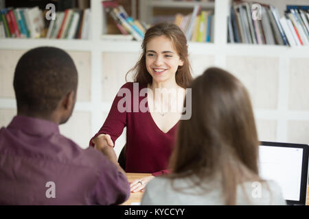 Smiling confident female applicant shaking hand of african hr manager making good first impression, employer congratulates - Stock Photo