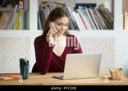 Smiling girl using laptop making answering call sitting at home office desk, happy student talking on phone looking - Stock Photo